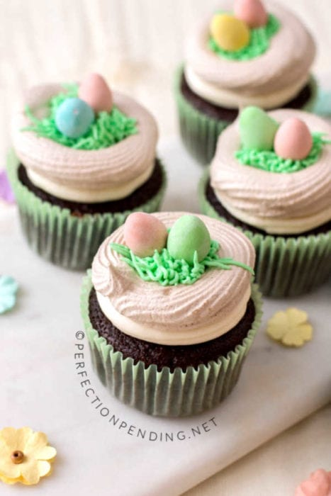 These chocolate cupcakes with a meringue bird's nest are perfect for your Easter party or Spring fun. With buttercream grass and bright colorful easter eggs, these fun Meringue Robin's egg nests make the perfect addition to your Easter chocolate cupcake. #Eastercupcakes #birdnestcupcakes #springcupcakes #Easterdessertidea